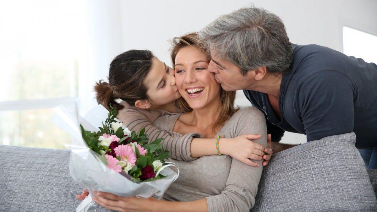 Семья празднует день матери с букетом цветов