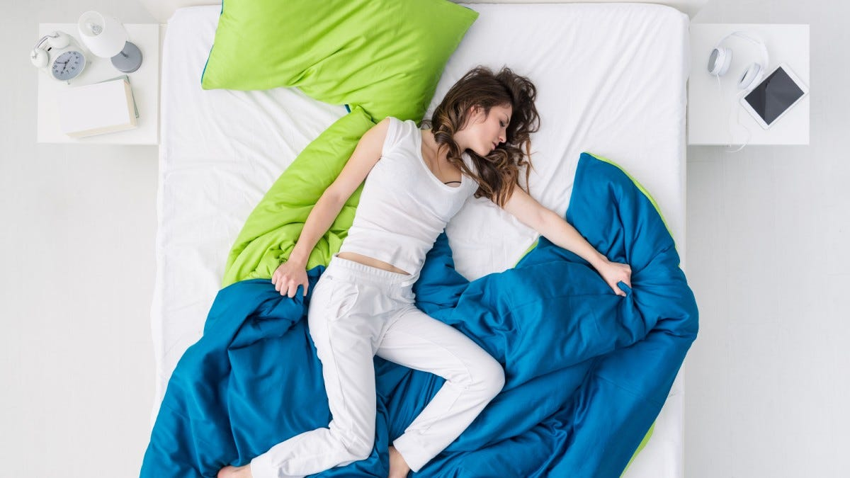 Woman sleeping on a bed, trying to stay cool at night