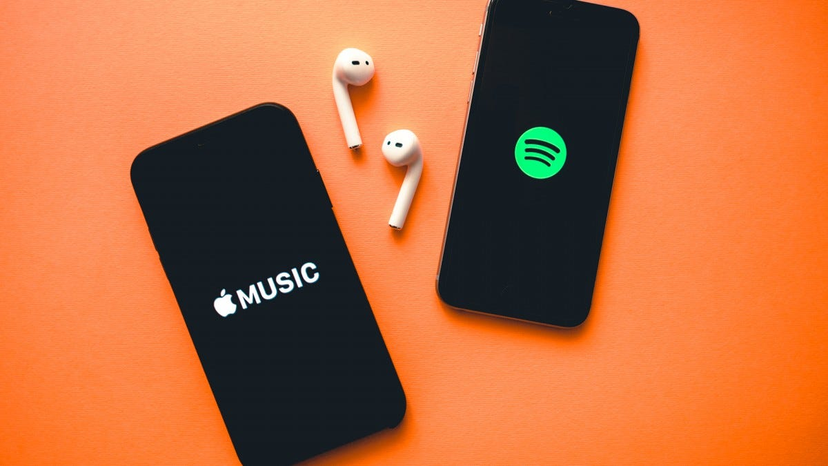 Two phones display the Spotify and Apple Music logos.