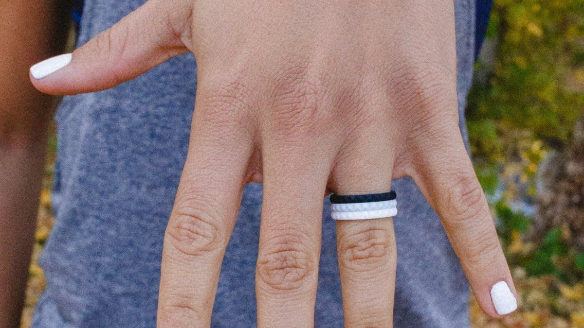Enso stackable rings in a stacked patter of black, grey, and white.