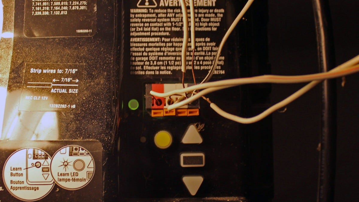 A close up of garage door wiring with four wires inserted to terminals.