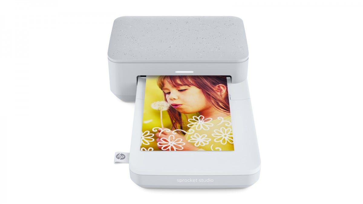 The Sprocket Studio printer printing a photo of a little girl holding a dandelion.