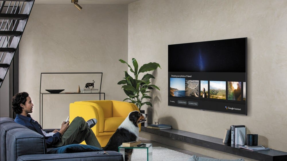 A man looking at a Samsung TV with Google Assistant on it.