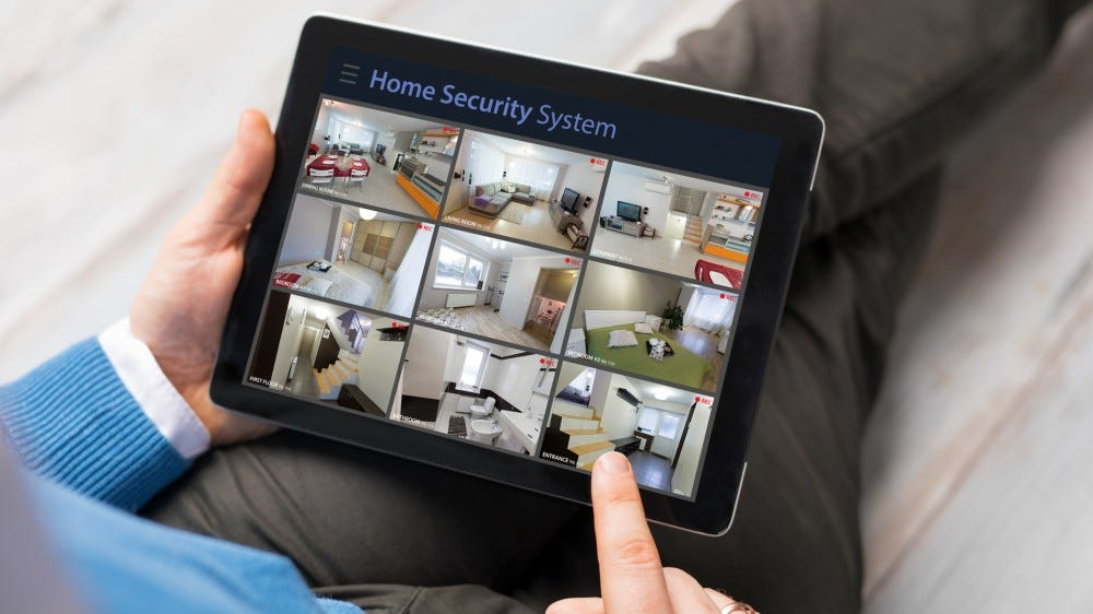 A man looking at home security system on a tablet