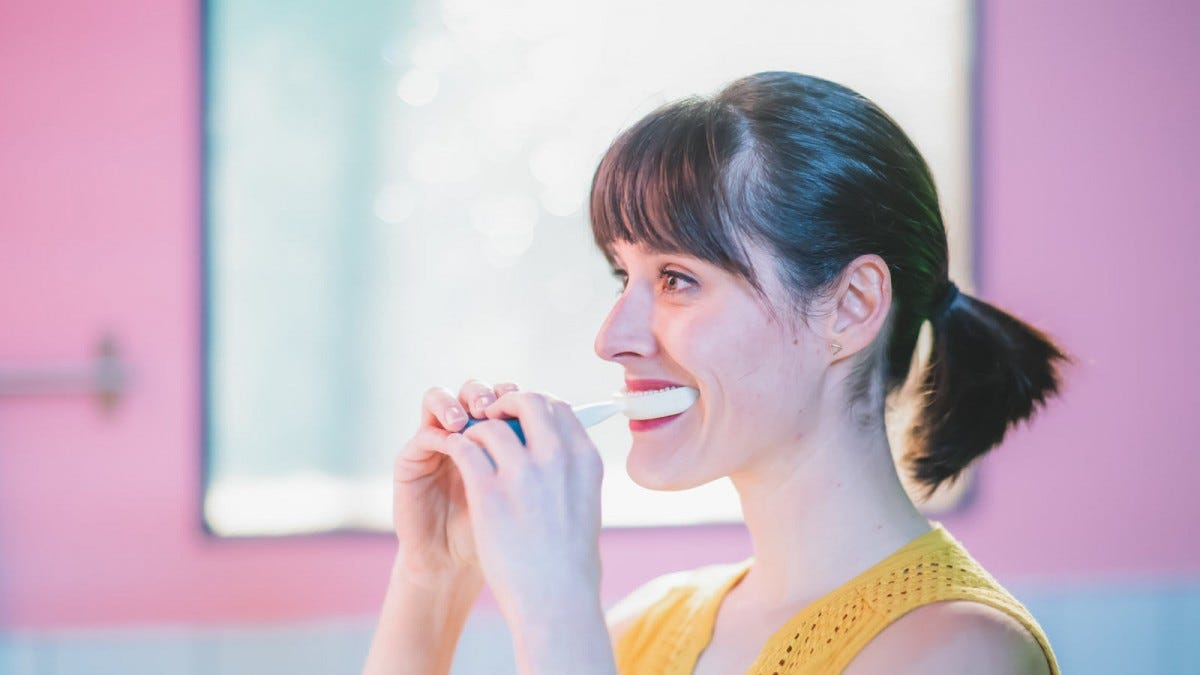A woman with a mouth guard attached to a handle in her mouth, brushing her teeth.