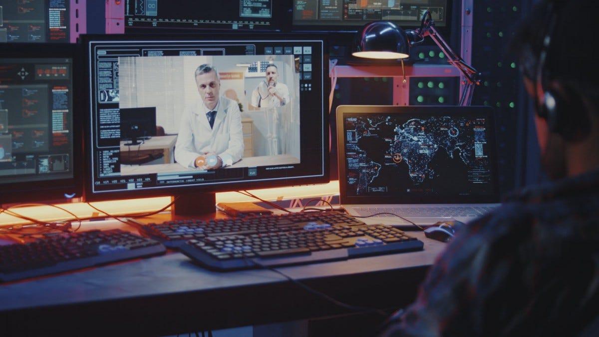 Một tin tặc trong một căn phòng tối tăm lắng nghe cuộc gọi Zoom cho các bác sĩ.