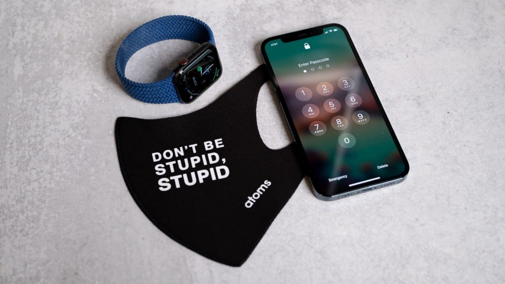 An Apple Watch and iPhone next to a face mask.