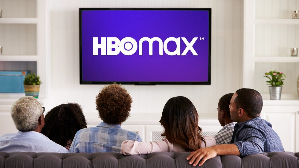 A family is sitting around a TV watching HBO Max.
