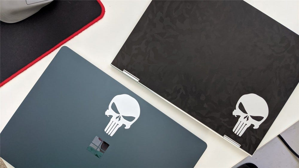 The Pixelbook with a black camo skin and surface laptop 3, both with Punisher stickers