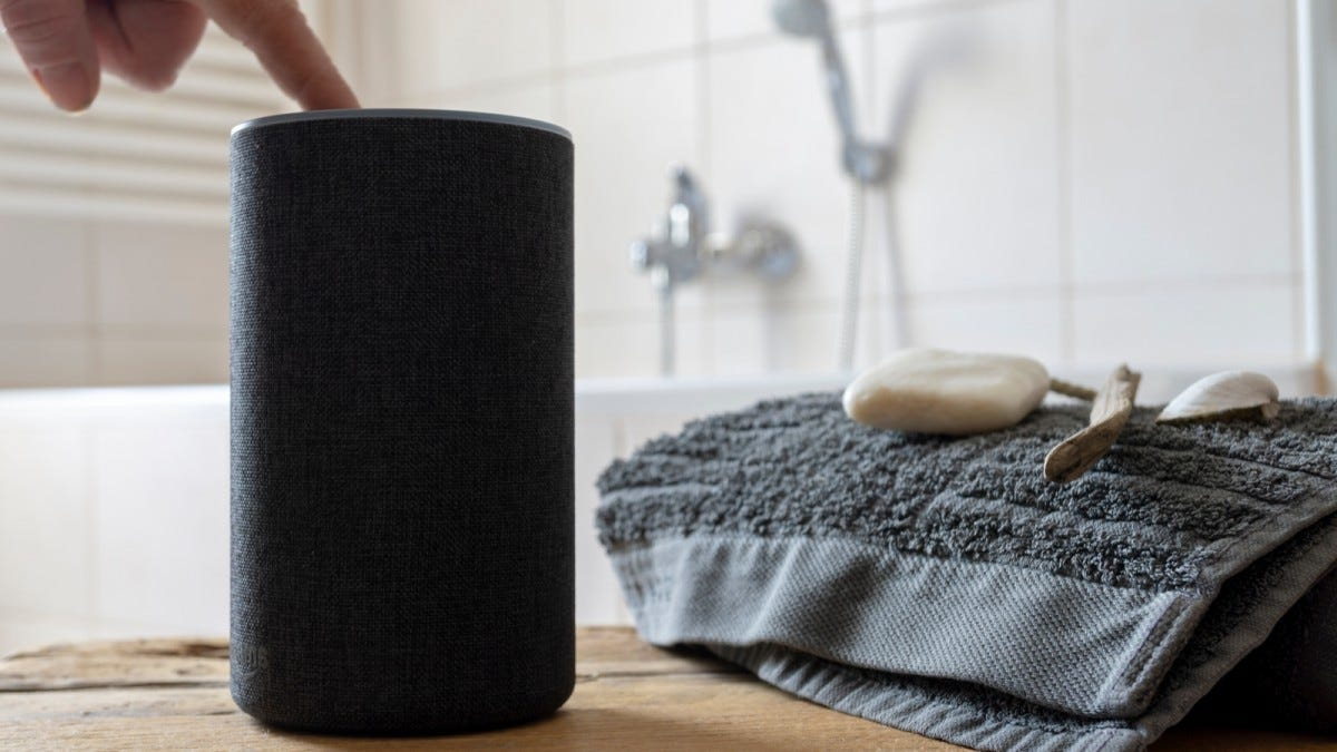A bluetooth speaker next to a bathtub