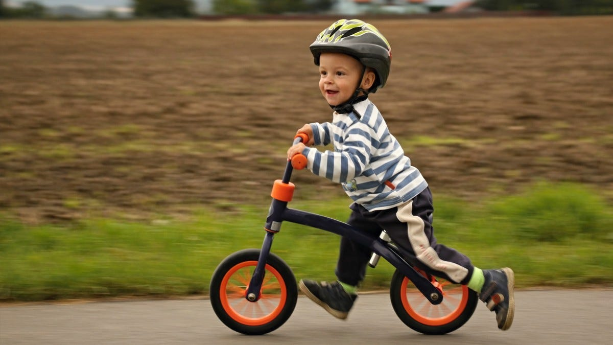 A toddler riding a balance bike