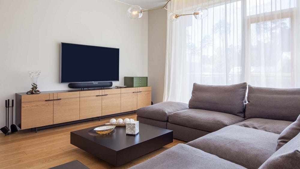 A modern living room with a sectional couch and a flat screen television.