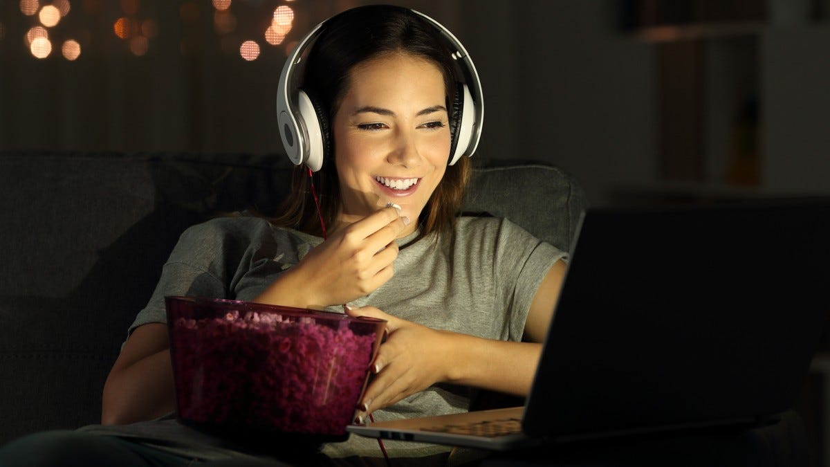 A girl eating popcorn while video chatting and watching Netflix with friends.