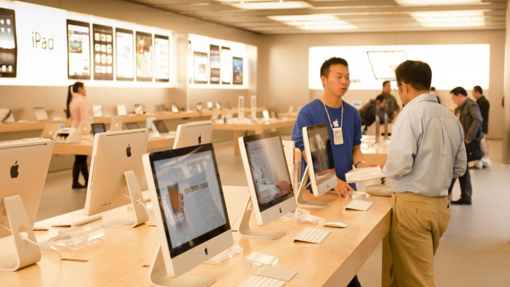 A young Apple sales assistant talks to a customer next to iMacs in the Apple Store interior shop
