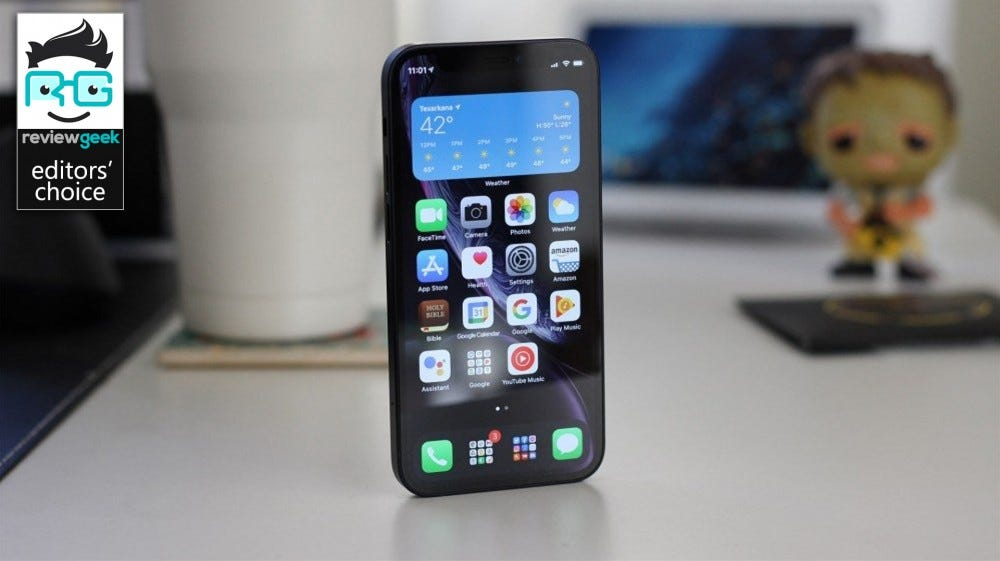 The iPhone 12 Mini in black on a white desk, trinkets in the background