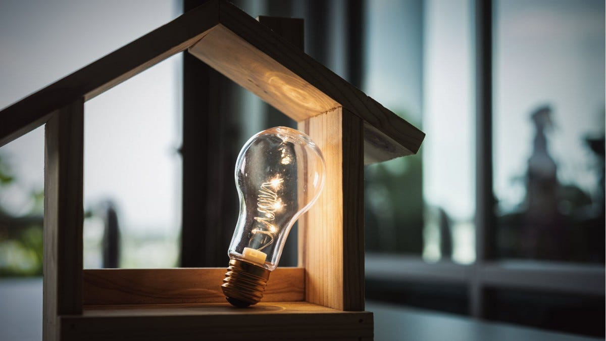 A light bulb leaning against the inside of a model-size, wooden house frame.