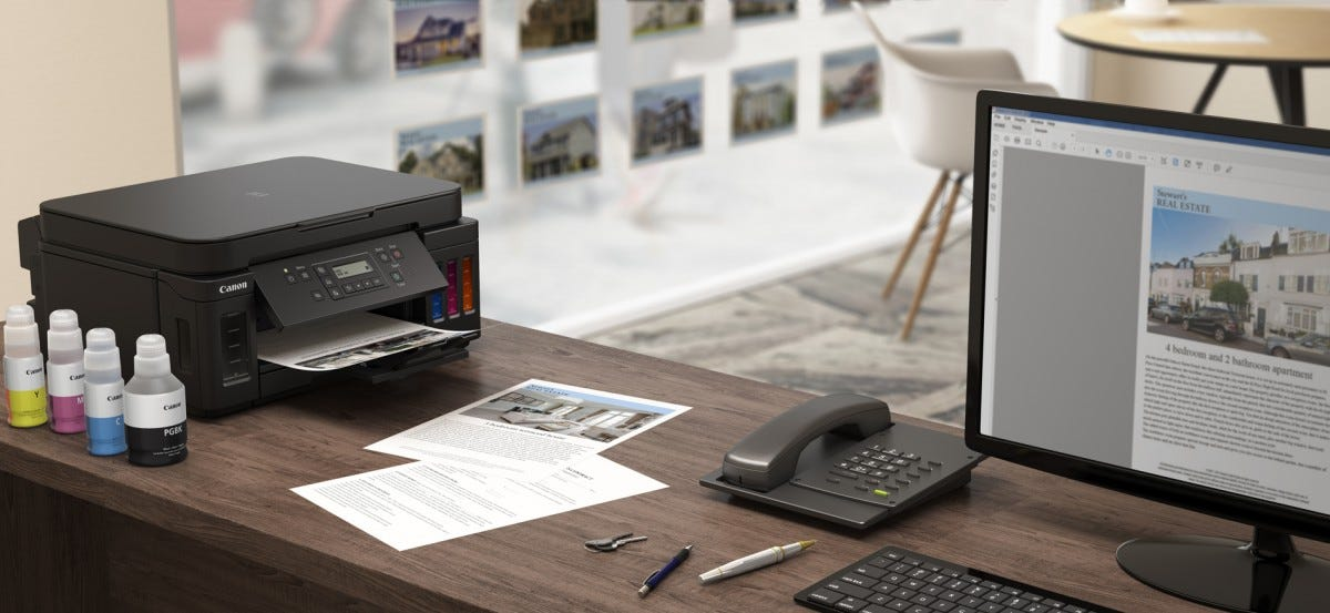 A Canon all-in-one printer sitting on a desk next to color and black ink refill bottles.