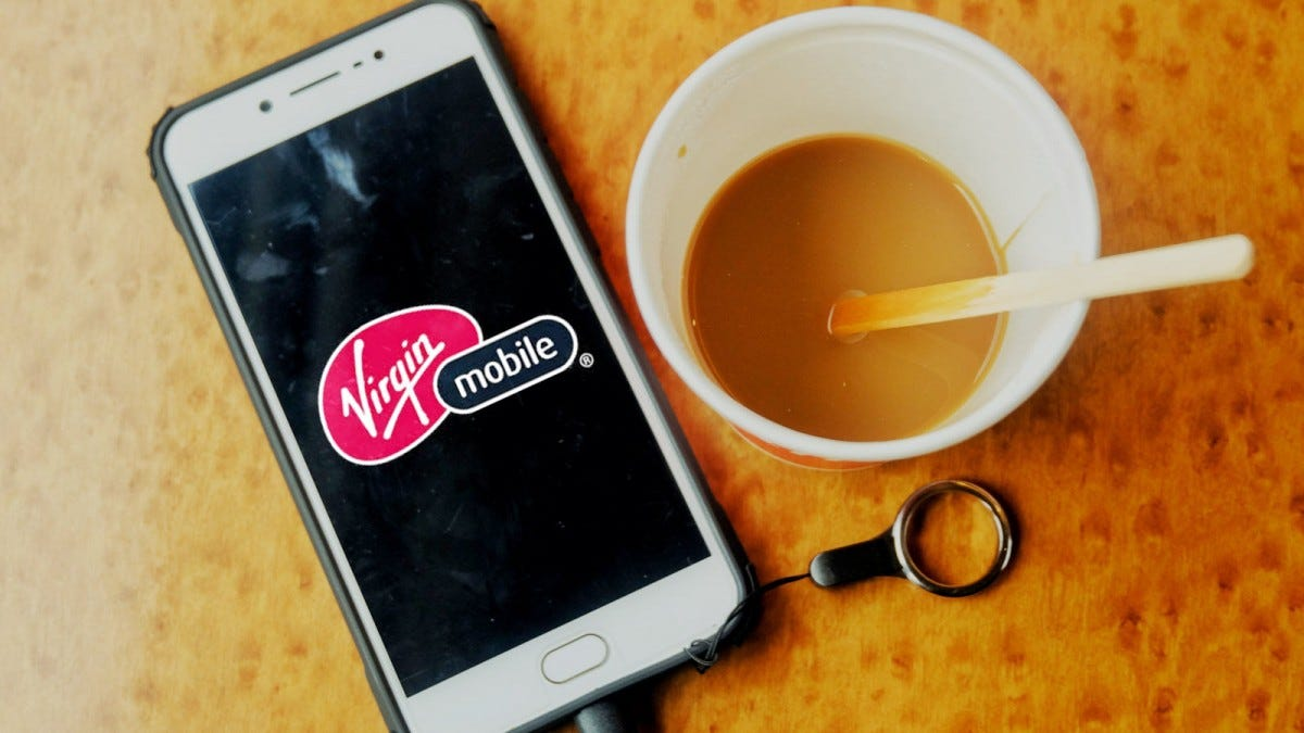 A Samsung Galaxy Phone with the Virgin Mobile logo displayed, laying next to a cup of coffee.