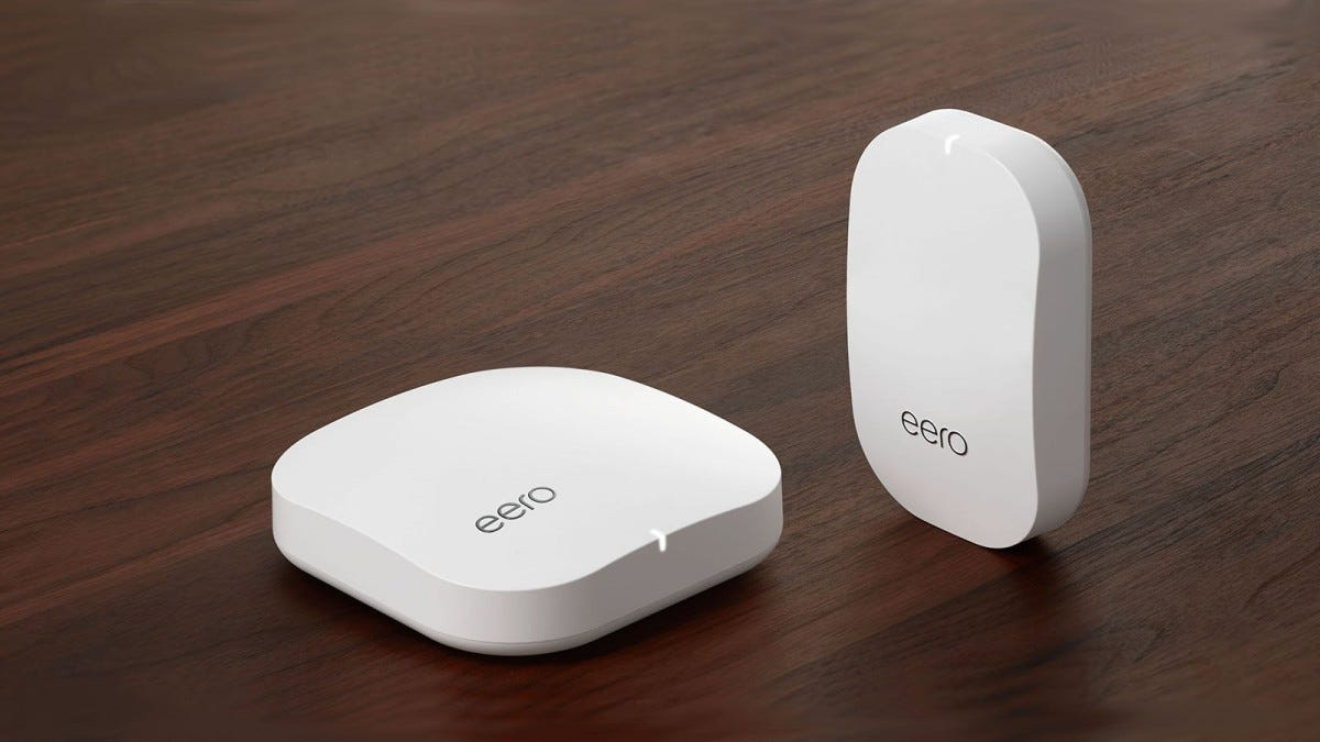 An eero router and beacon on a wood floor.