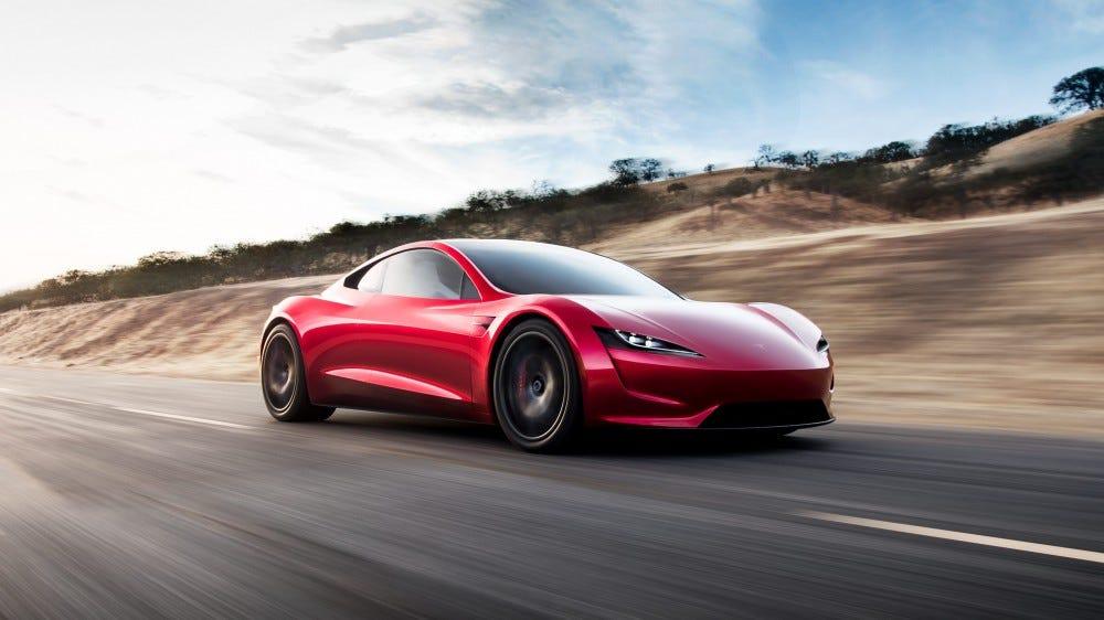 A Tesla Roadster car speeding along a highway.