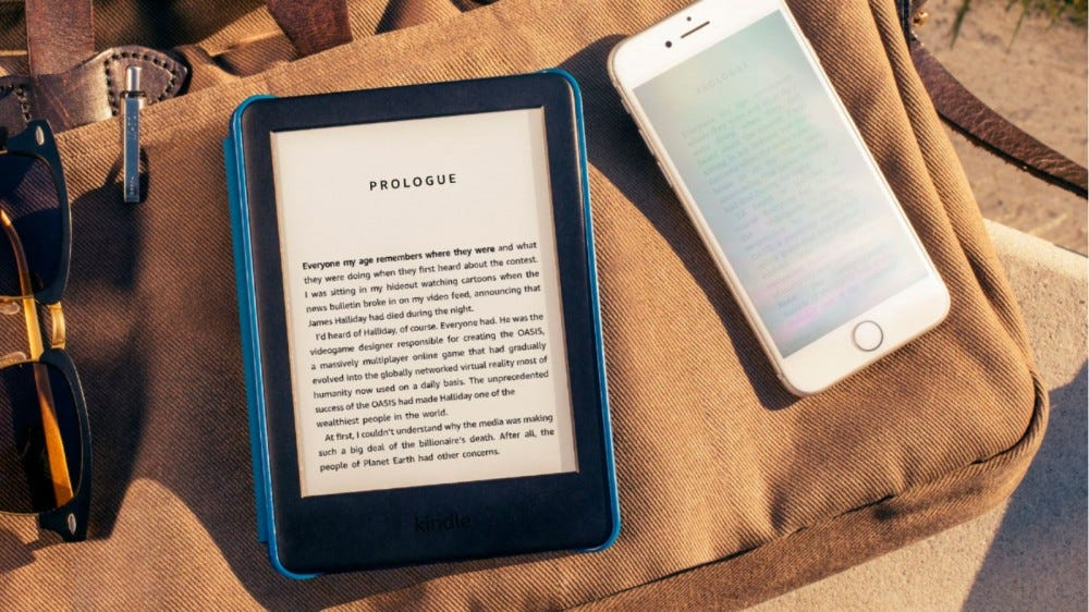 Amazon Kindle laying on a bag in sunlight.