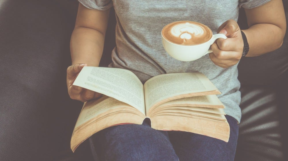 Young woman reading a book and holding a cup of coffee