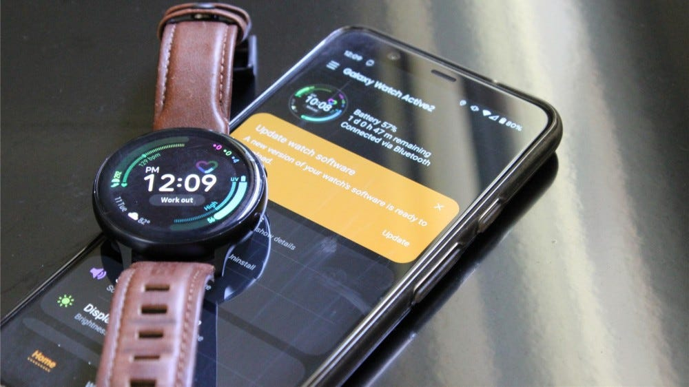The Samsung Galaxy Watch Active 2 laying on top of the Pixel 4 XL