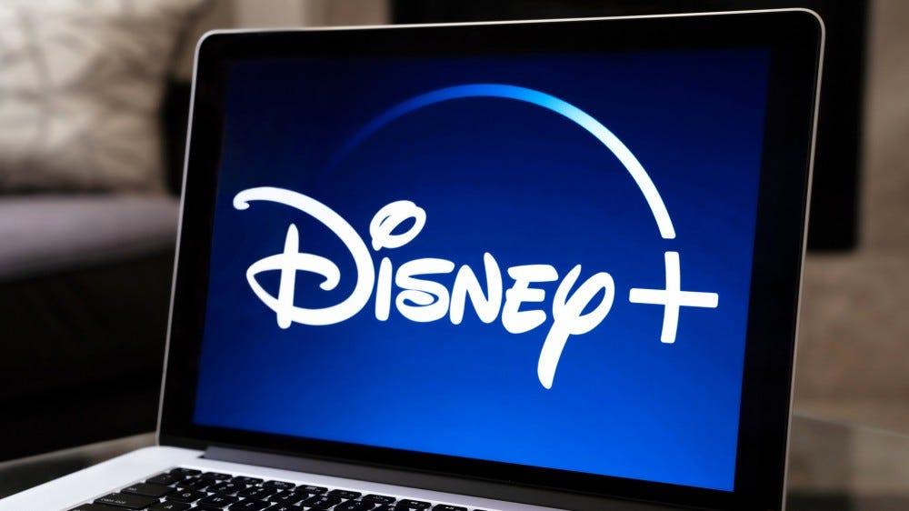 Disney + logó nyitva az Apple laptopon, egy tál popcorn mellett
