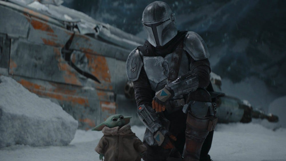 The child and the mandalorian stand on an icy world.