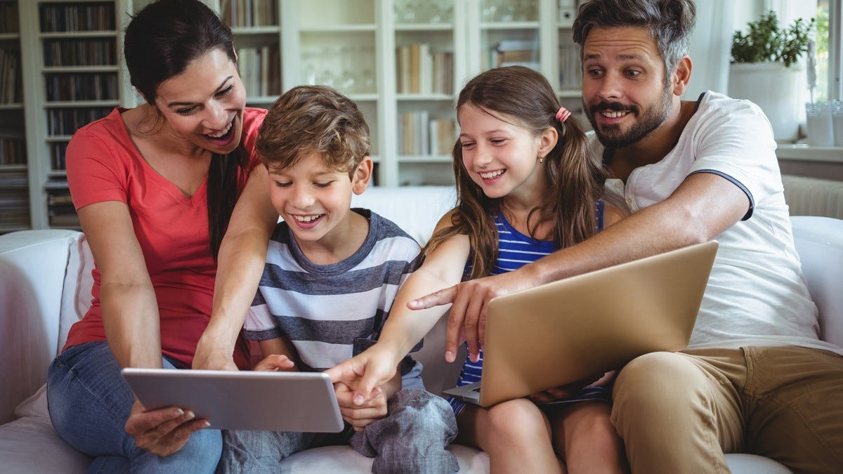 A family plays on their laptops and tablets.