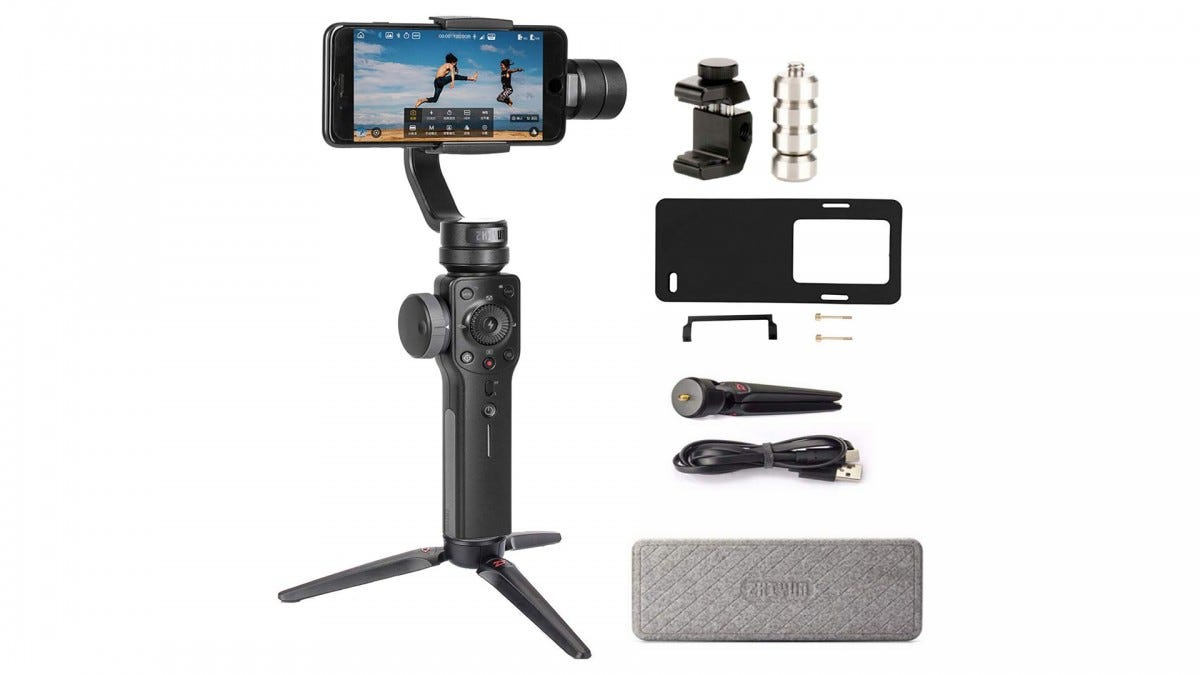 The Zhiyun Smooth 4 gimbal holding a smartphone and sitting next to its accessories.