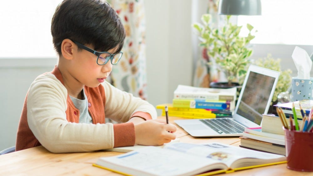 A smart preteen boy sitting at a table writing homework and preparing for an online exam