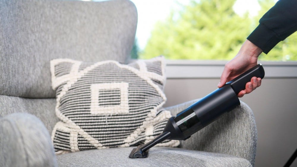 A Wyze hand vacuum cleaner for cleaning a chair.