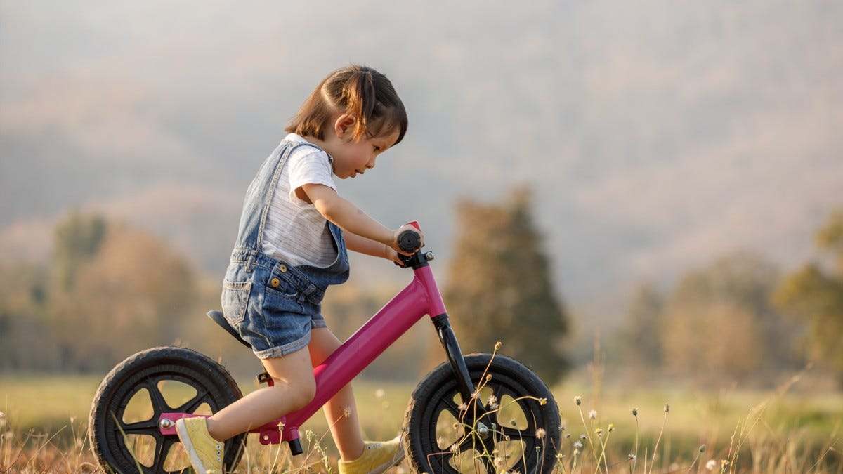 A toddler riding on a balance bike.