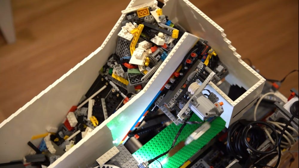 A mess of LEGO bricks moving up a conveyor belt.