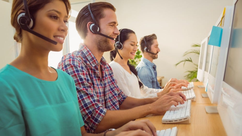 Business customer service team working together at a call center wearing headsets typing on computer