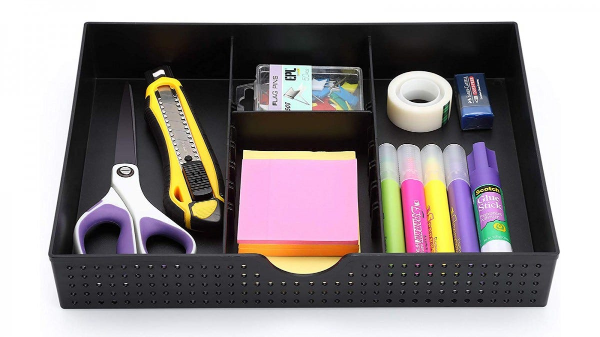 The CAXXA Three-Slot Drawer Organizer holding scissors, a box cutter, paper clips, Post-its, tape, highlighters, and a glue stick.