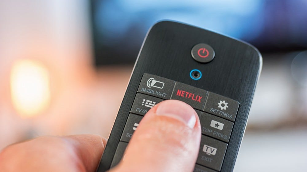 Man holds a remote control and pushes a Netflix button on it