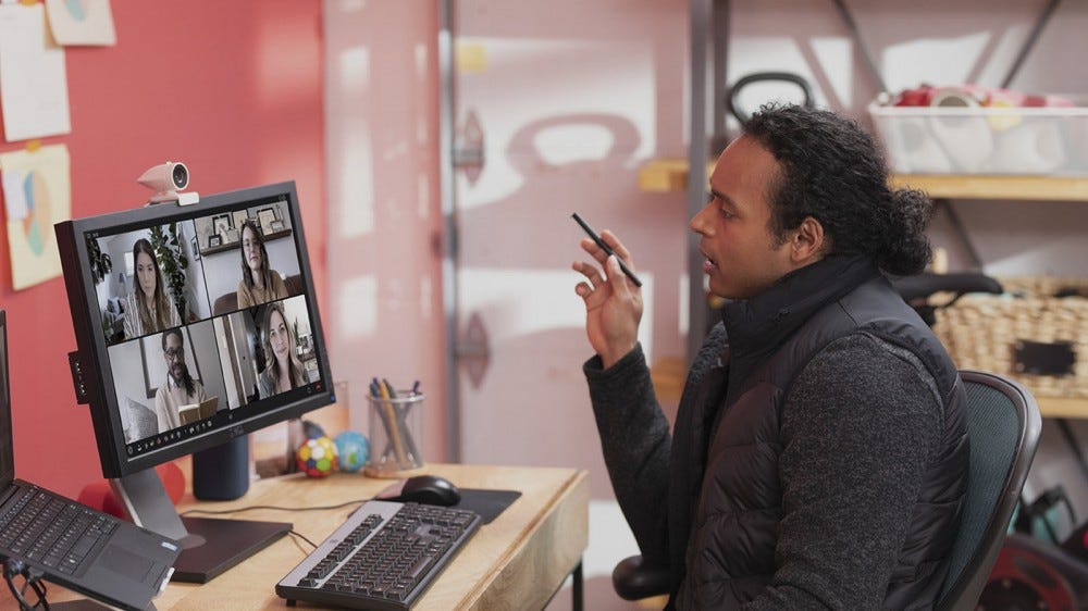 Egy férfi videohíváson, egy kis fehér webkamerával.