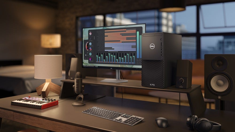 The new Dell XPS desktop on a desk with a wireless keyboard and monitor.