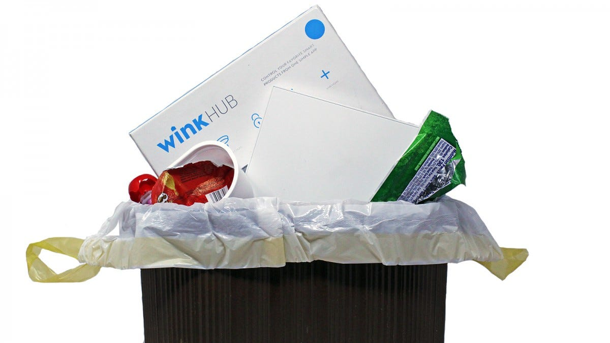 A Wink Hub and Box in a trash can with other garbage.