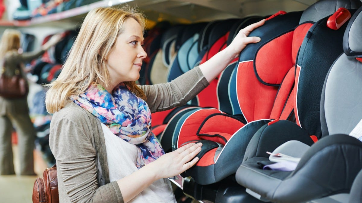 A woman looking at car seats in a store.