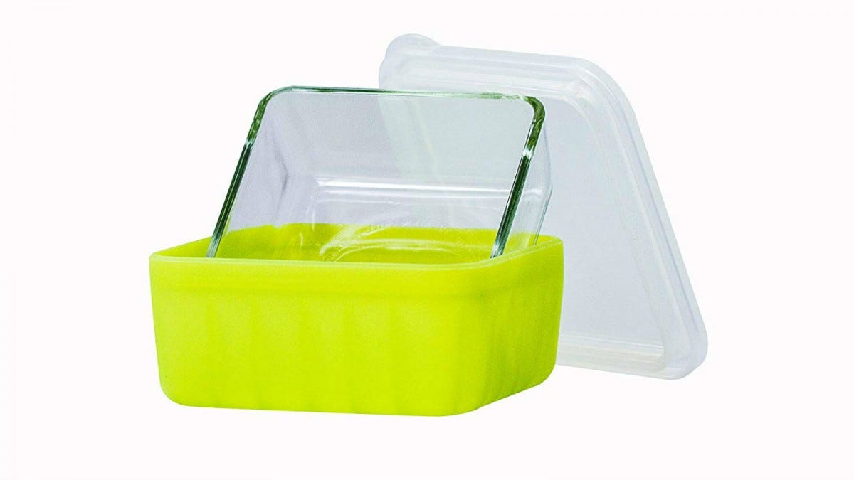 A lime-green Frego glass food container sitting up inside its silicone container with the lid resting against it.
