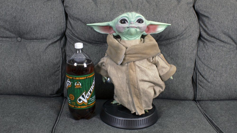 Baby Yoda is larger than a 2 liter bottle of soft drink.