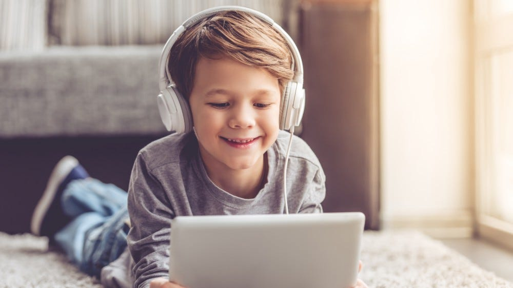 Little kid wearing headphones while using a tablet