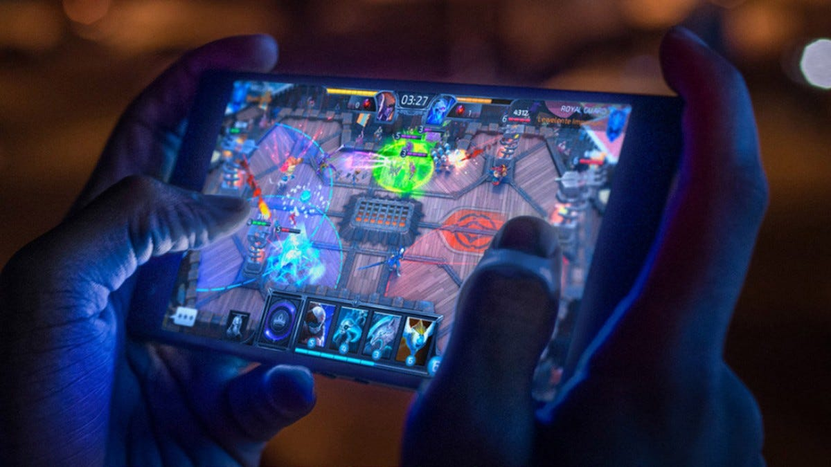 Man's hands playing a game on a Razer phone.
