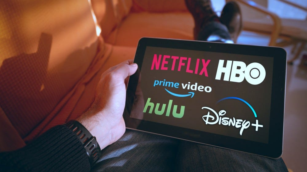 Man holds a tablet with Netflix, Hulu, Amazon Video, HBO, and Disney+ logos