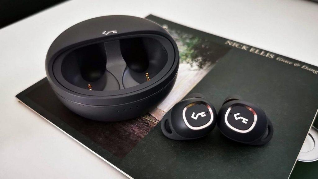 both t10 headphones next to open case displaying logo