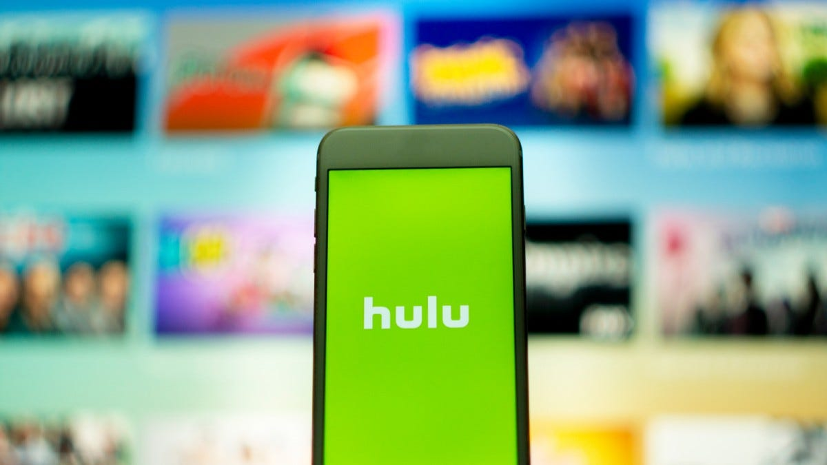 Hulu service logo on smartphone in front of TV
