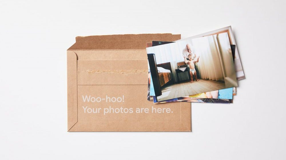Google Photos premium print series delivery package, opened with prints on top